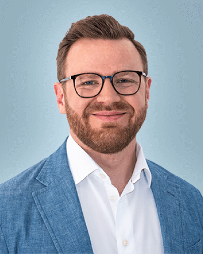 smiling man with beard and glasses wearing white shirt and blue jacket